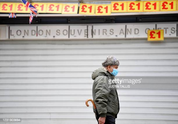 Pedestrian wearing a face covering walks past a souvenir shop, closed due to Covid-19, in central London on March 24, 2021. - Britain's annual...