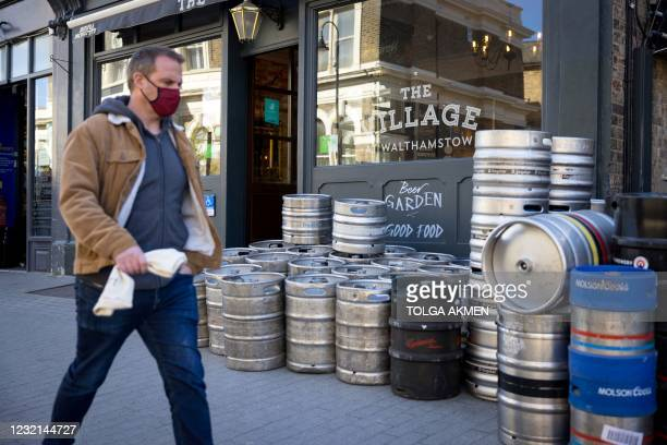 Pedestrian wearing a face covering walks past empty beer barrels waiting to be collected, outside The Village Pub in Walthamstow, northeast London on...
