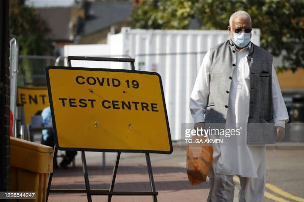 A pedestrian wearing a face mask as a precaution against the transmission of the novel coronavirus walks past a sign pointing the way to a covid19...