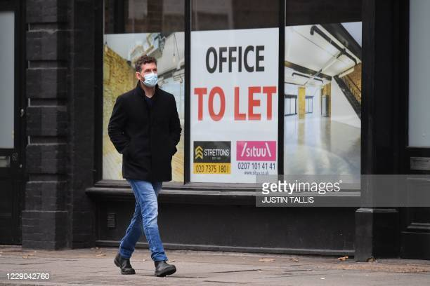Pedestrian wearing a face mask as a precaution against the transmission of the novel coronavirus walks past a boarded up office space which is to let...