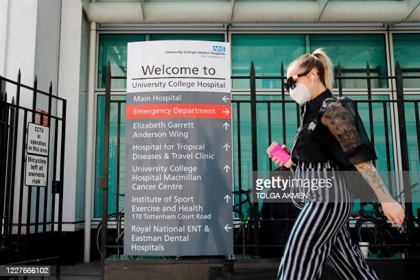 Pedestrian wearing a face mask as a precaution against the transmission of conoronavirus walks past signage outside University College Hospital in...