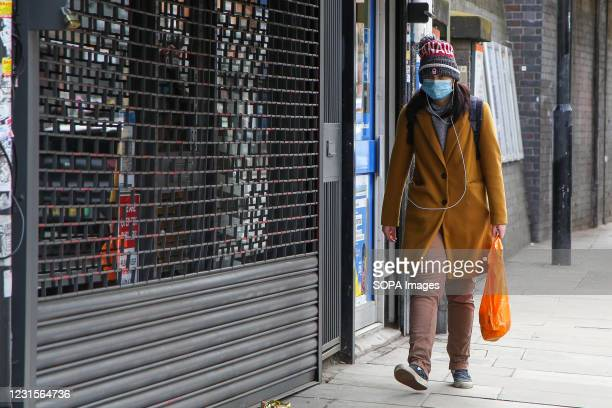Pedestrian wearing a face mask as a precaution against the spread of covid-19 walks past a shop in London during the lockdown. Prime Minister Boris...