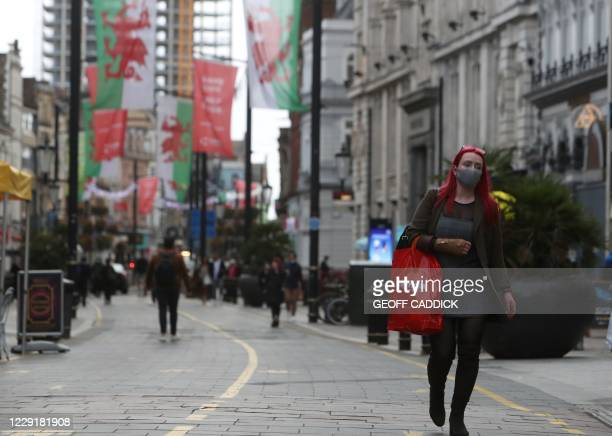 Pedestrian wearing a face mask carries shopping in Cardiff, south Wales on October 20 ahead of a short, two-week lockdown due to begin on October 23,...