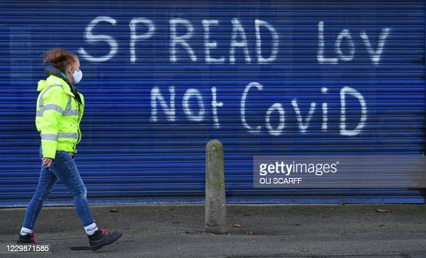 "Pedestrian wearing a face mask due to the coronavirus pandemic, walks past graffiti reading ""Spread Lov, not COVID"" on the shutters of a closed..."