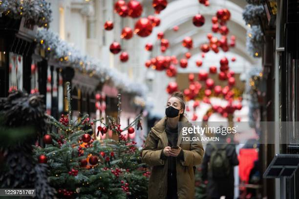Pedestrian wearing a face mask due to the COVID-19 pandemic, walks past Christmas-themed window displays inside Burlington Arcade in central London,...