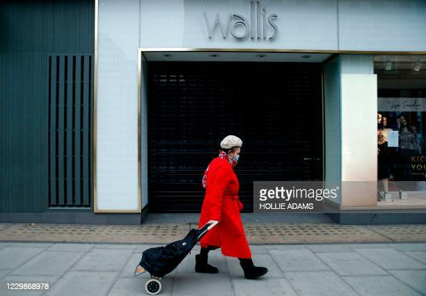 Pedestrian wearing a face mask due to the COVID-19 pandemic, walks past a shuttered and closed-down Wallis clothes store, operated by Arcadia, in...