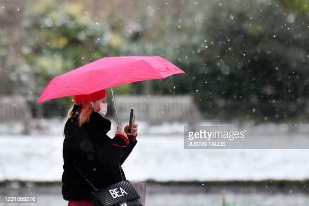 Pedestrian wearing a face mask or covering due to the COVID-19 pandemic, shelters from the snow beneath an umbrella in Green Park in central London...