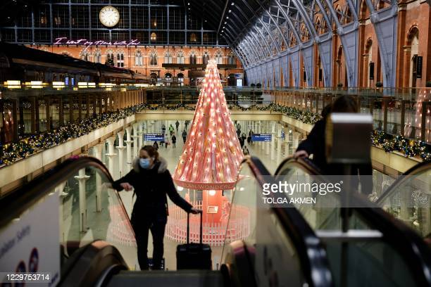 "Pedestrian wearing a face mask or covering due to the COVID-19 pandemic, travels on an escalator near the ""Tree of Hope"" Christmas tree, installed..."