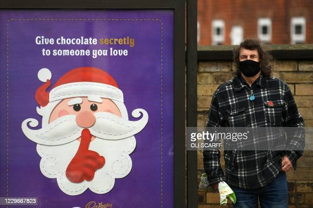 Pedestrian wearing a face mask or covering due to the COVID-19 pandemic, stands alongside an advert for Christmas advert for Cadbury's chocolate in...