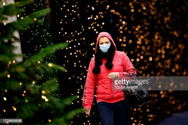 Pedestrian wearing a face mask or covering due to the COVID-19 pandemic, walk past Christmas-themed window display at Selfridges department store in...
