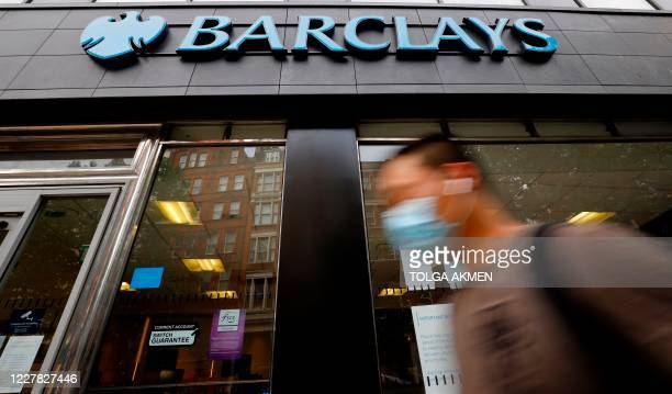 A pedestrian wearing a face mask or covering due to the COVID19 pandemic walks past a branch of a Barclays bank in central London on July 29 2020...