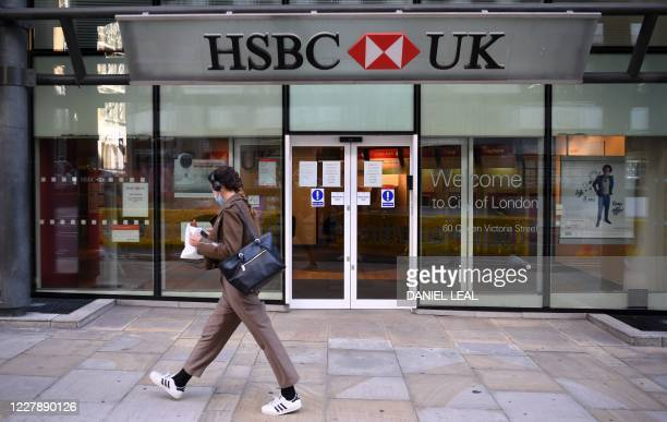 Pedestrian wearing a face mask or covering due to the COVID-19 pandemic, walks past a branch of a HSBC bank in central London on August 3, 2020. -...