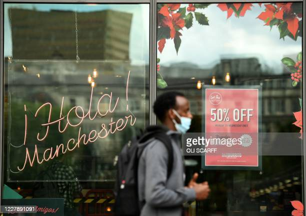 A pedestrian wearing a face mask or covering due to the COVID19 pandemic walks past a sign promoting the British Government's Eat out to Help out...