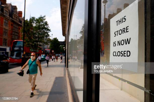 A pedestrian wearing a face mask or covering due to the COVID19 pandemic walks past a sign in the window of a store alerting customers that the shop...