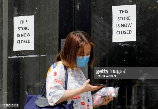 Pedestrian wearing a face mask or covering due to the COVID-19 pandemic, walks past a sign in the window of a store alerting customers that the shop...