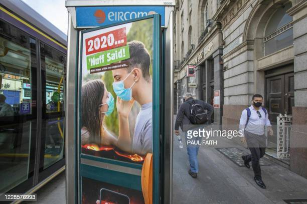 Pedestrian wearing a face mask or covering due to the COVID-19 pandemic, walks past an advert depicting a young couple wearing facemasks, and the...