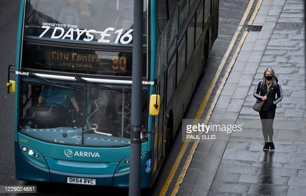 Pedestrian wearing a face mask or covering due to the COVID-19 pandemic, walks past a bus in Liverpool, north west England on October 12 as new local...