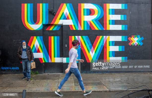 """Pedestrian wearing a face mask or covering due to the COVID-19 pandemic, walks past a mural reading """"U Are Alive..... So get your head out of your..."""