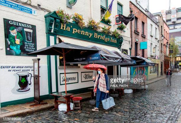 Pedestrian wearing a face mask or covering due to the COVID-19 pandemic, walks past a pub in Dublin on October 19 amid reports that further lockdown...