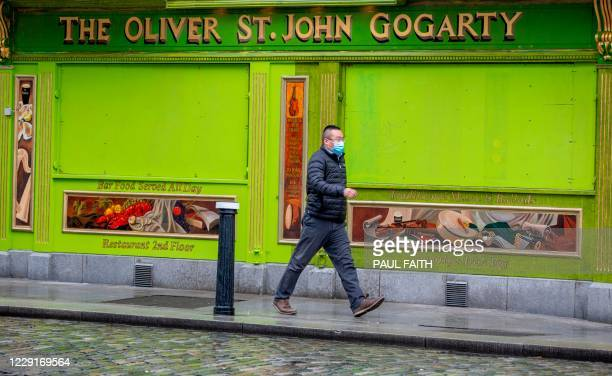 Pedestrian wearing a face mask or covering due to the COVID-19 pandemic, walks past a closed-down pub in Dublin on October 19 amid reports that...