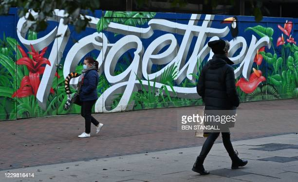 """Pedestrian wearing a face mask or covering due to the COVID-19 pandemic, walks past graffiti reading """"Together"""" in Royal Tunbridge Wells in Kent,..."""