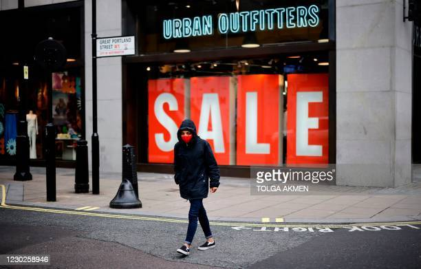 """Pedestrian wearing a face mask or covering due to the COVID-19 pandemic, walks past a giant """"Sale"""" sign in the window display of an Urban Outfitters..."""