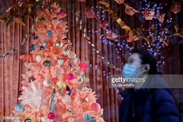 Pedestrian wearing a face mask or covering due to the COVID-19 pandemic, walks past a Christmas-themed display in a shop window on Oxford Street in...