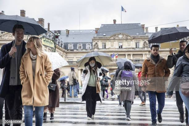 A pedestrian wearing a face mask uses a road crossing near the Louvre Museum which is closed due to staff worries over the coronavirus outbreak in...