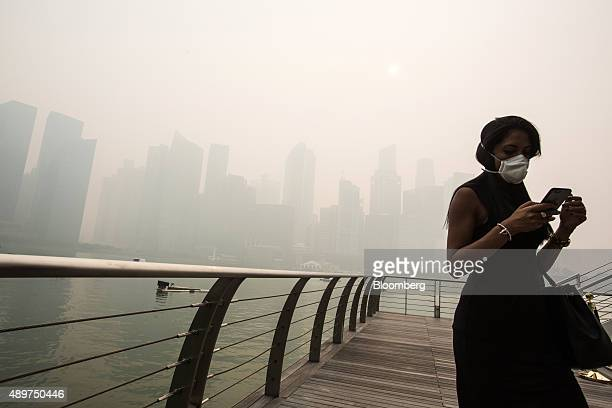Pedestrian wearing a face mask uses a smart device at Marina Bay as buildings in the central business district stand shrouded in smog in Singapore,...