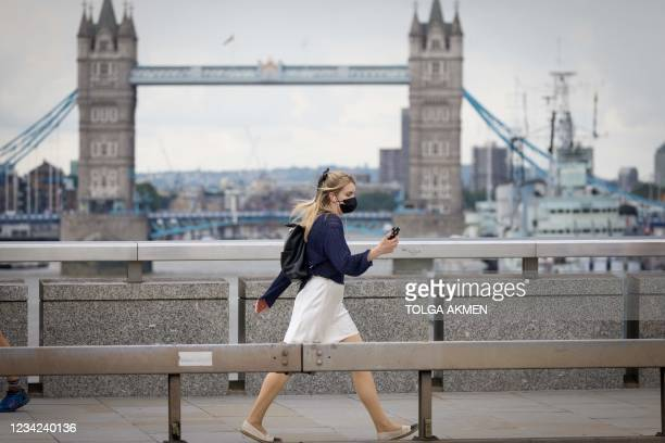 Pedestrian wearing a face mask walks across London Bridge in central London on July 27, 2021. - Prime Minister Boris Johnson called for caution...