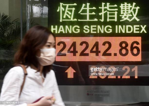 Pedestrian wearing a face mask walks by an electronic screen displaying the Hang Seng Index on October 7, 2020 in Hong Kong, China.