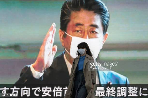 Pedestrian wearing a face mask walks in front of a monitor displaying an image of Japan's Prime Minister Shinzo Abe during a news broadcast on April...