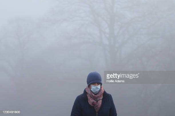 Pedestrian wearing a face mask walks in the fog at Parliament Hill in Hampstead Heath on January 9 in London, England. The Met Office have issued a...