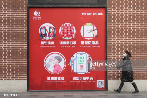 Pedestrian wearing a face mask walks past a COVID-19 public health advice poster outside a cinema on February 23, 2021 in Shanghai, China.