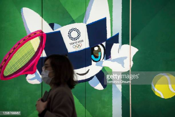 Pedestrian wearing a face mask walks past a display with an illustration of the 2020 Tokyo Olympic and Paralympic Games mascot character Miraitowa on...