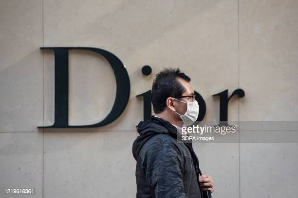 Pedestrian wearing a face mask walks past a French Christian Dior luxury goods store and logo seen in Hong Kong.