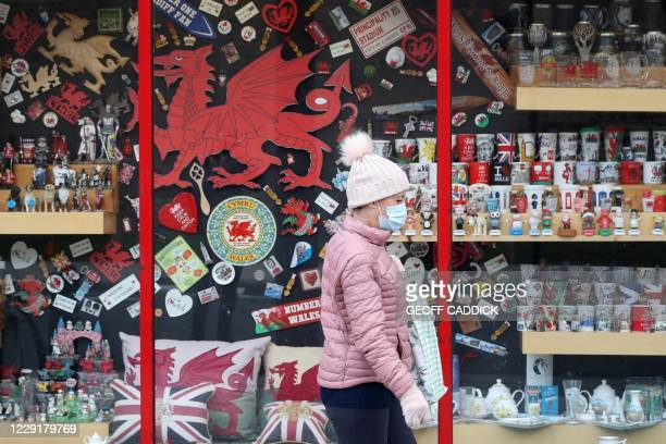 Pedestrian wearing a face mask walks past a tourist shop in Cardiff, south Wales on October 20 ahead of a short, two-week lockdown due to begin on...