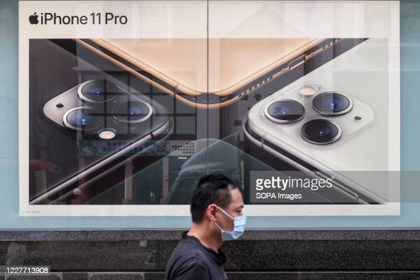 A pedestrian wearing a face mask walks past an American multinational technology company Apple Iphone 11 Pro advertisement in Hong Kong