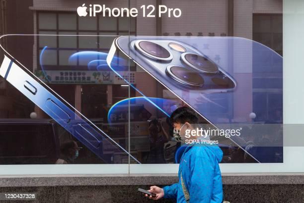 Pedestrian wearing a face mask walks past an American multinational technology company Apple Iphone 12 Pro advertisement in Hong Kong.