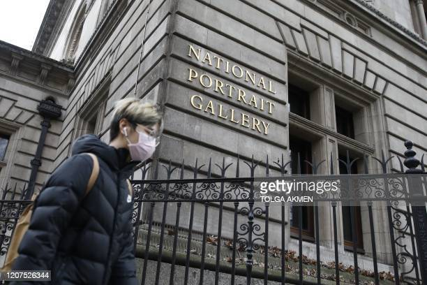 Pedestrian wearing a face mask walks past the National Portrait Gallery in central London on March 17, 2020 after it was announced that the gallery...
