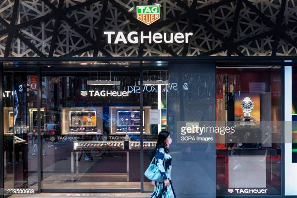 A pedestrian wearing a face mask walks past the Swiss luxury watchmaker brand Tag Heuer store in Hong Kong