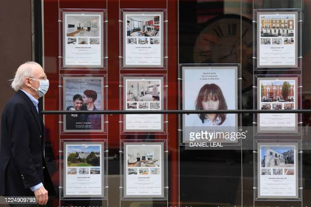 Pedestrian wearing a face mask walks past the window of an estate agents in London on July 6, 2020. - According to reports Britain's Chancellor of...