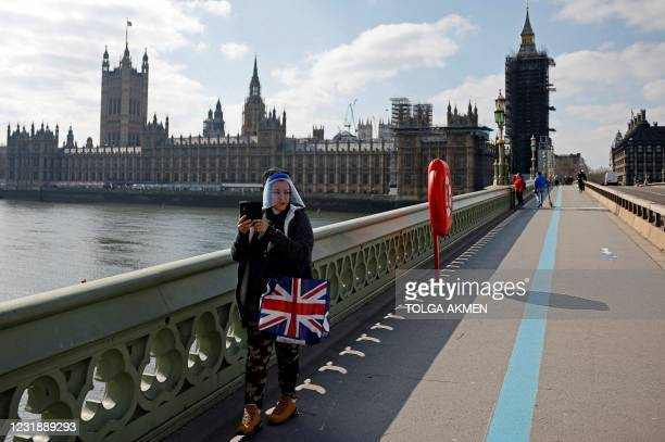 Pedestrian wearing a face shield due to Covid-19, stands with a Union flag-themed bag as they make a video call in front of the Palace of...