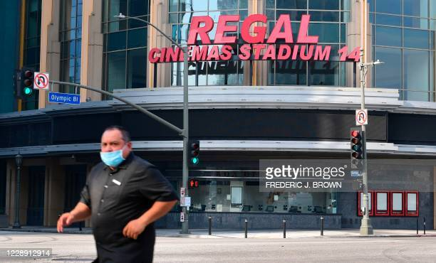 Pedestrian wearing a facemask due to the coronavirus pandemic crosses a street across from Regal Cinemas L.A. Live on October 5, 2020 in Los Angeles,...