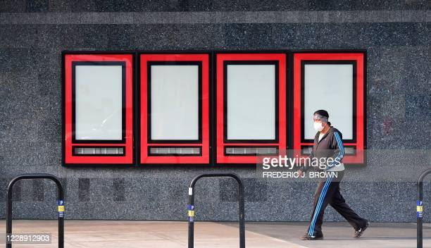 Pedestrian wearing a facemask due to the coronavirus pandemic walks past empty displays where upcoming movies were once displayed as Regal Cinemas...