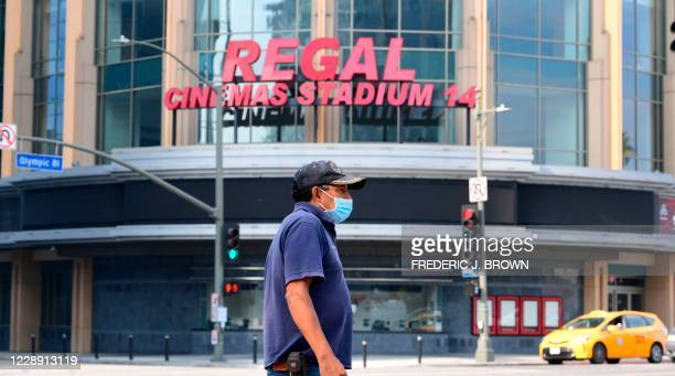 Pedestrian wearing a facemask due to the coronavirus pandemic walks past a closed Regal Cinemas L.A. Live on October 5, 2020 in Los Angeles,...