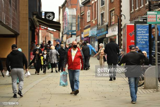Pedestrian wearing a facemask walks in central Rochdale, greater Manchester, northwest England on July 30, 2020. - Rochdale reportedly faces harsher...