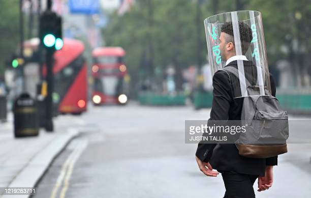 TOPSHOT A pedestrian wearing a form of PPE of a perspex fullface covering as a precautionary measure against COVID19 walks across Oxford Street in...