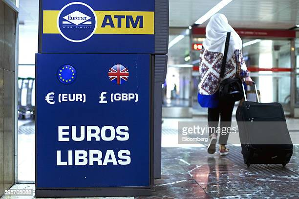 A pedestrian wearing a headscarf wheels her suitcase past an automated teller machine operated by Euronet Worldwide Inc advertising euros and...