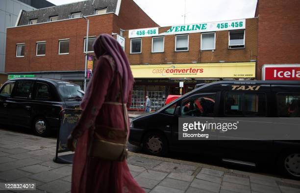 Pedestrian wearing a hijab passes a row of taxi vehicles parked opposite a Cash Converters International Ltd. Pawnbrokers in Luton, U.K., on...